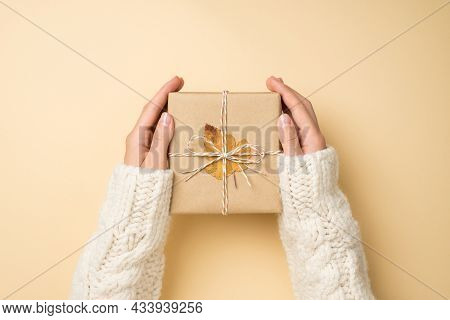 First Person Top View Photo Of Hands In White Sweater Holding Craft Paper Giftbox With Twine Bow And