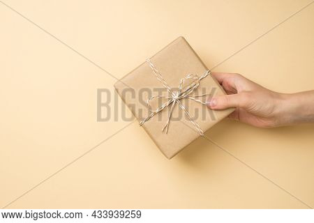 First Person Top View Photo Of Female Hand Holding Craft Paper Giftbox With Twine Bow On Isolated Be