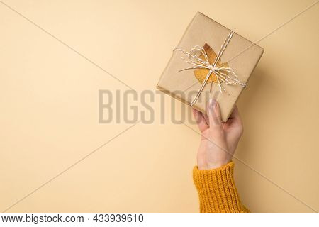 First Person Top View Photo Of Woman Hand In Yellow Knitted Sweater Holding Stylish Craft Paper Gift