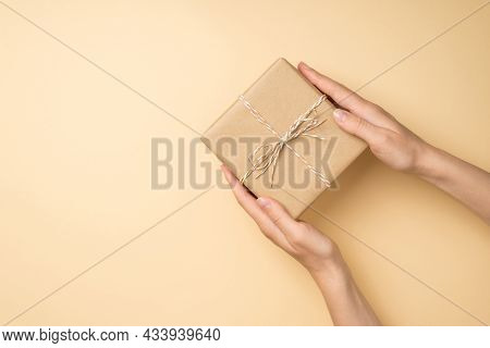 First Person Top View Photo Of Female Hands Holding Craft Paper Giftbox With Twine Bow On Isolated B