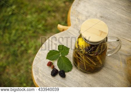 Top View Of A Warm Glass Teapot, Green Tea Leaves And Lemongrass On The Wooden Desk At Fall Day.