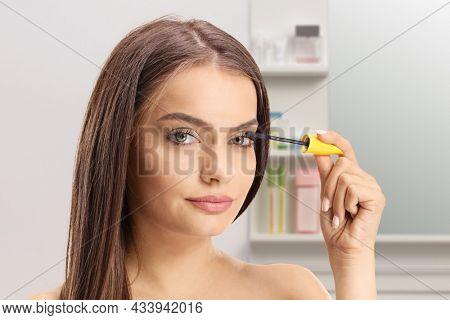 Beautiful young woman applying mascara on eyelashes in a bathroom