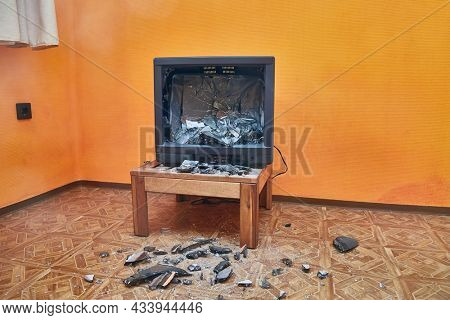 Olt tube TV set smashed with an axe, glass CRT imploding, pieces in the room everywhere