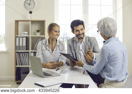 Happy Couple Signing Contract During Meeting With Banking Agent, Realtor Or Mortgage Broker
