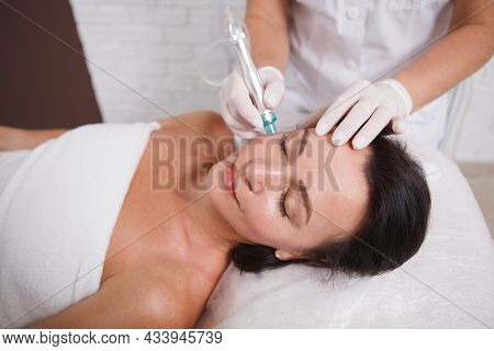 Attractive Mature Woman Getting Hydra Facial Procedure By Cosmetologist