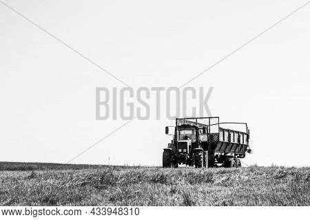 Belarus, Vitebsk Region, July 9, 2020. Tractor With A Trailer In The Field For Agricultural Work. Ha