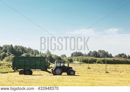 Tractor With A Trailer In The Field For Agricultural Work. Hay Making, Grassland. Copy Space.