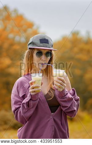 A Girl In A Purple Shirt With Purple Lips Drinks Two Milkshakes From Tubules At The Same Time On An