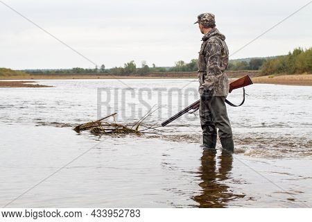 A Hunter With A Shotgun In His Hand Is Standing In Shallow Water. He Wades Across The River.