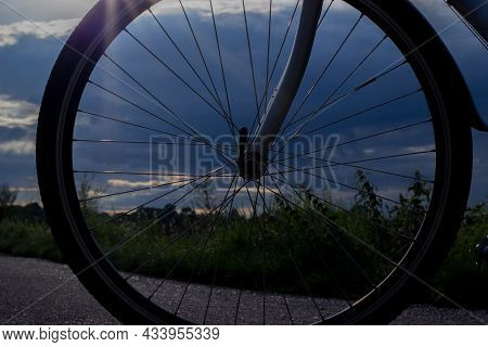 View Through The Bike Wheel On The Meadow At Sunset In Blue