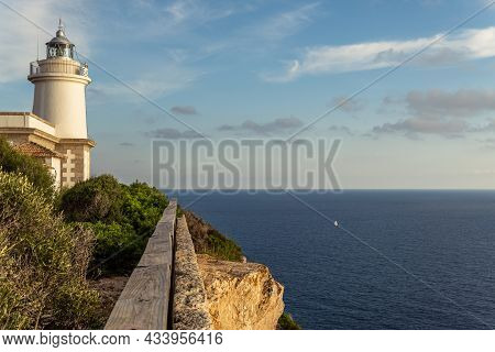 Cap Blanc Lighthouse On The Rocky Coast Of The Island Of Mallorca. In The Background S Seascape Of T