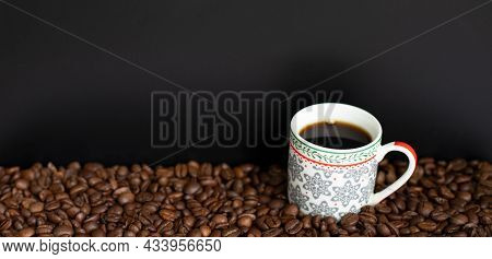 A Beautiful Colorful Coffee Cup Full Of Black Coffee On A Dark Background With Fresh Roasted Coffee
