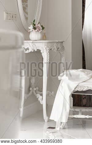 White Silk Dressing Gown On Chair Near White  Console Table In Beautiful Light Interior. Wedding Con