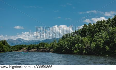 An Inflatable Boat With People Is Floating On The Blue River. Lush Green Vegetation On The Banks.  A