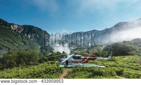 On A Green Meadow, On The Landing Pad, There Is A Helicopter. A Mountain Range Against The Blue Sky.