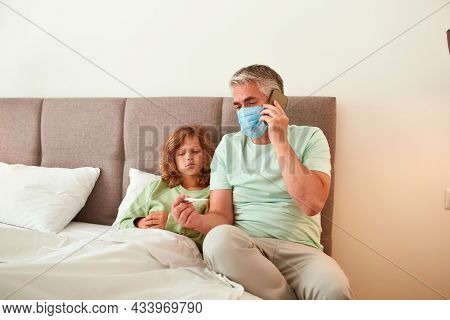 Dad In Facemask Talk With Doctor Consult About Sick Teen Son Have High Temperature Feel Unhealthy. C