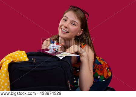 A Young Pretty Smiling Woman Waiting For The Flight Sitting On Her Knees Leaning On A Suitcase Holdi