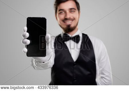 Cheerful Young Bearded Waiter In Elegant Uniform Demonstrating Modern Mobile Phone With Empty Black