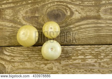 Bright Unripe Yellow Tonatoes Close Up Flat Lay Photo On Brown Textured Wooden Background Top View