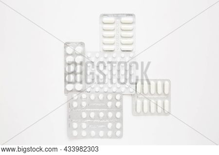 Blisters Of White Pills On A White Background, Top View. Various Medications, Tablets, Medication Ca