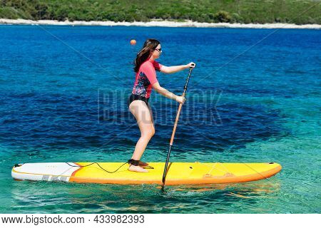 Young Active Girl On A Sup Board With A Paddle In Her Hand - Shot From The Side, Calm Surface Of The