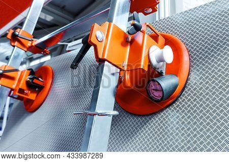 Suction Cups For Transporting Large Sheets Of Metal. Equipment For The Installation Of Iron Structur