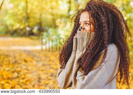Beautiful Afro-haired Woman Wearing Warm Sweater Walk In Autumn Park At Sunny Warm Day And Feel Cold