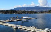 Three float planes docked in a harbour. poster