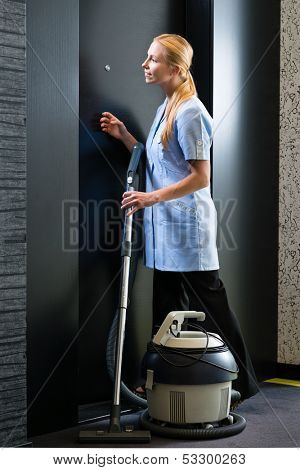 Hotel room service - young chambermaid standing in front of a suite door in a hotel with a vacuum cleaner to clean the room
