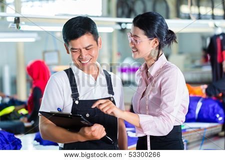Indonesian Worker or foreman and dressmaker or designer looking on Clipboard in a Asian factory for garments