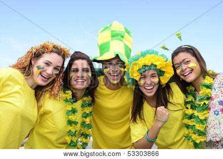 Group of happy brazilian soccer fans commemorating victory, with the flag of Brazil swinging in the air.