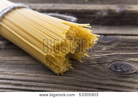 Bundle of long spaghetti on a old grungy wooden desk.