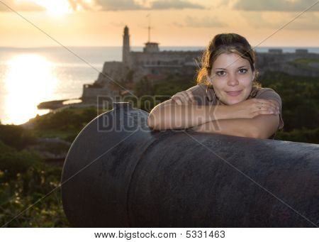 Beautiful Girl Smiling Near An Old Cannon