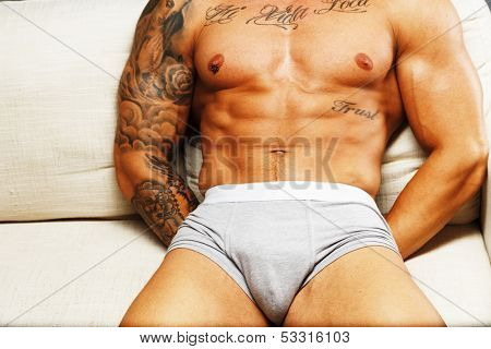 Man with beautiful muscular tattooed torso in underwear lying on sofa
