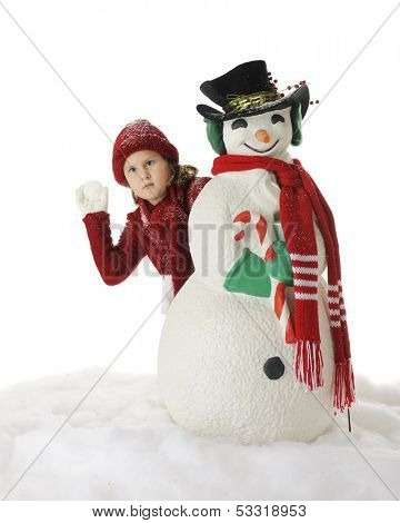 An elementary girl seriously contemplating the snowball throw she'll take while hiding behind a Christmasy Snowman.  On a white background.
