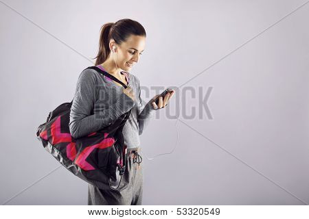 Fitness Woman With Gym Bag Listening Music