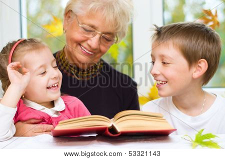 Great-grandmother Reading A Book For Grandchildren