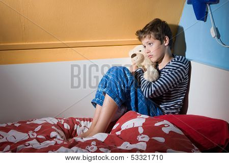 A young boy is sitting afraid and depressed on his bed in his bed room poster