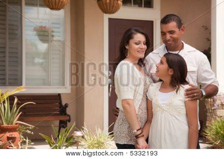 Pequeña familia hispana frente a su casa