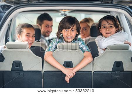 Playful kids posing in the back of a car with their parents in background