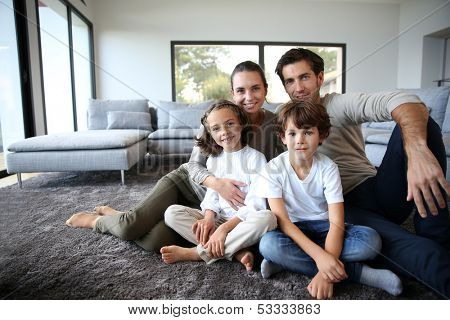 Happy family portrait at home sitting on carpet