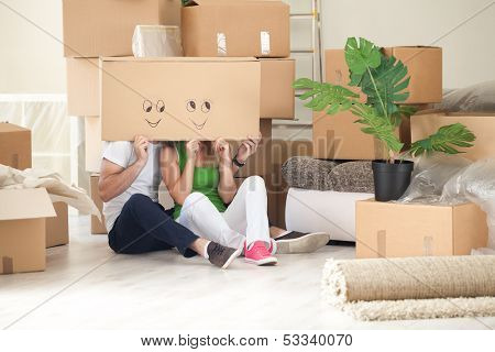 Happy couple in their new home having fun - moving concept