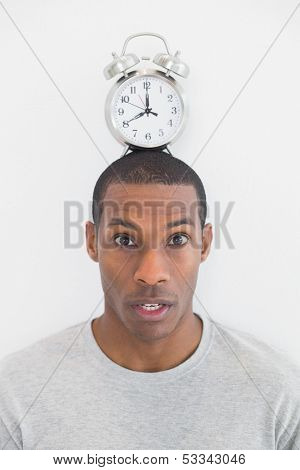 Close up portrait of a man with an alarm clock on top of his head over white background