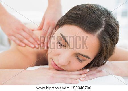 Close up of a beautiful woman enjoying shoulder massage at beauty spa