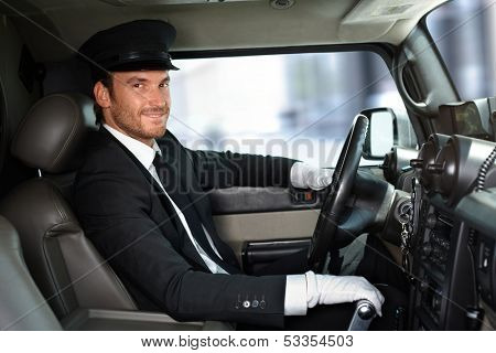 Handsome smiling chauffeur driving limousine.