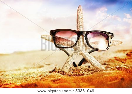 Funny starfish with sunglass on the sandy beach at ocean background poster