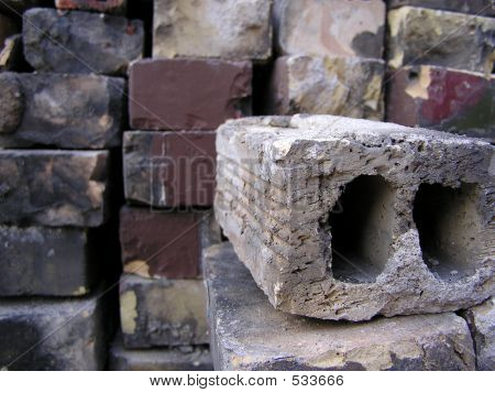 Stack Of Old Bricks With A Brick In Foreground