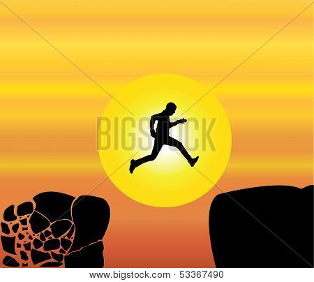 young fit man jumping from a crumbing mountain rock to another safer rock on a bright orange sky sun