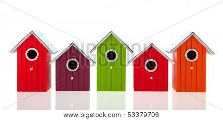 Colorful bird houses in a row isolated over white background