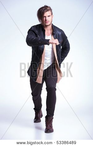 young man in leathe jacket in a fashion pose on studio background